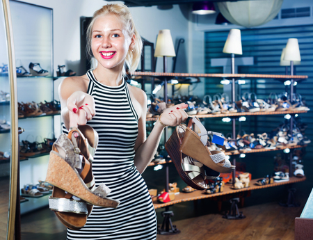 Happy beautiful young woman standing in boutique and having many shoes in hands
