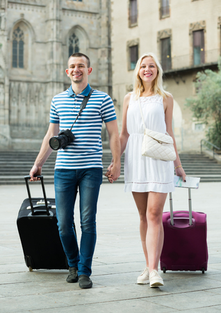 Laughing traveling man and woman walking together with luggage and looking around in city