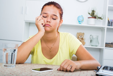 crying teenage girl looking at silent mobile phone indoors