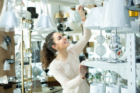 Portrait of young brunette choosing decorative interior lights for home in mall 版權商用圖片