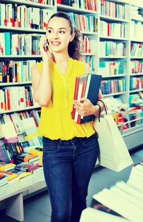 publishers: Glad beautiful woman chatting on mobile phone and taking literature books in store Stock Photo