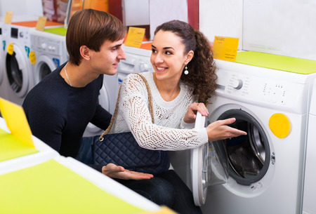 lavadora con ropa: Family couple buying new clothes washer in supermarket