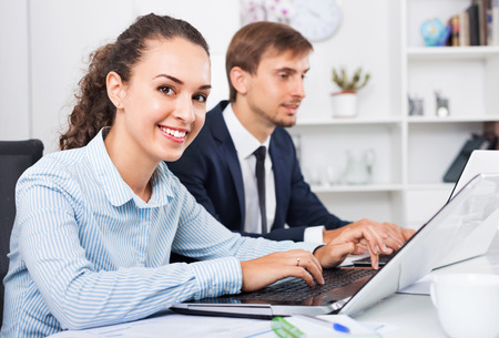 Glad friendly efficient business female assistant wearing formalwear using laptop in company office