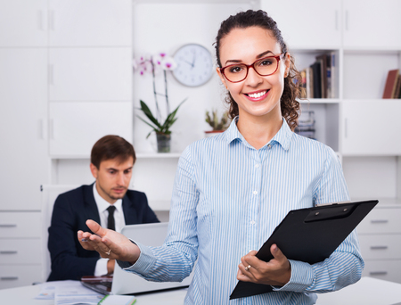 glad: Glad smiling efficient business female secretary having cardboard in hands and working in office