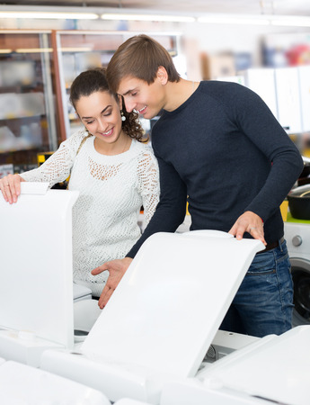 lavadora con ropa: Happy family couple buying new clothes washer in appliance store