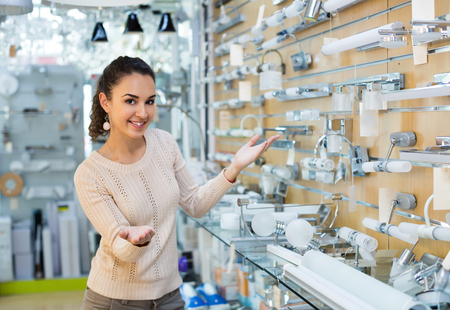 interior lighting: Adult girl selecting lighting units for interior in household store