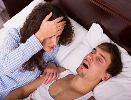 disturbed: Angry brunette wife disturbed with husband loud snoring Stock Photo