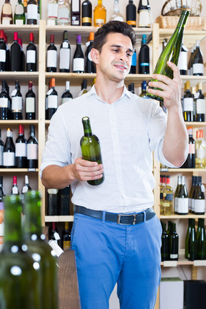 russian man: portrait of smiling russian man choosing bottle of wine in shop