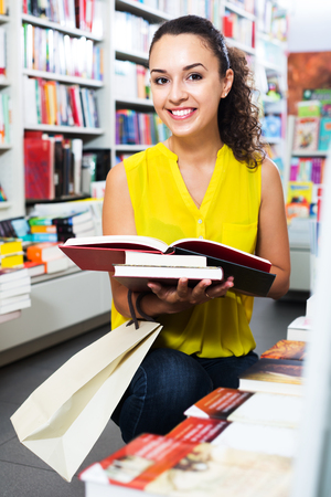 publishers: Portrait of glad young woman looking interested and reading textbook in book shop