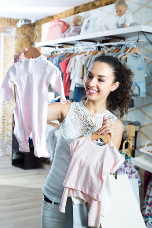 portrait of young smiling woman shopping baby sleepers in kids clothes store Stock Photo