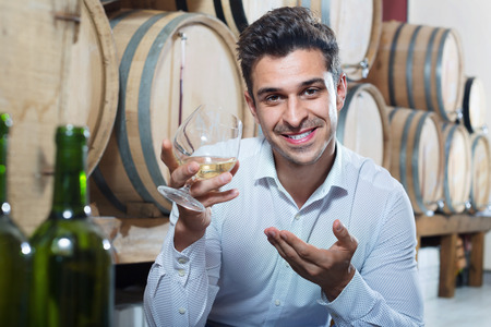 Portrait of positive man enjoying liquor sample in glass in section with woods