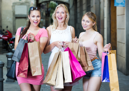 Three young positive girlfriends holding many shopping paper bags in town