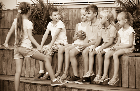 boys playing: Cheerful positive boys and girls in school age sitting and playing with ball outdoors
