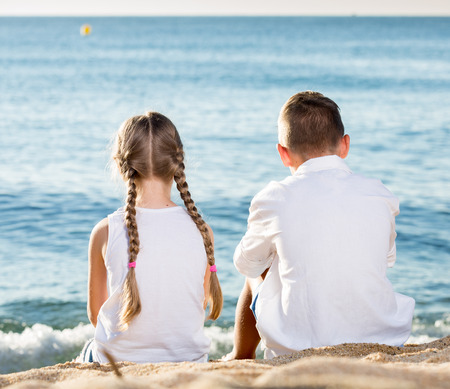 niños platicando: Two kids sitting on beach with back forward and looking at water