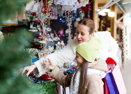 overspending: mother with daughte buying decorations for Xmas. Focus on woman