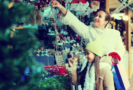 overspending: Little daughter with positive mom in Christmas market. Focus on woman Stock Photo