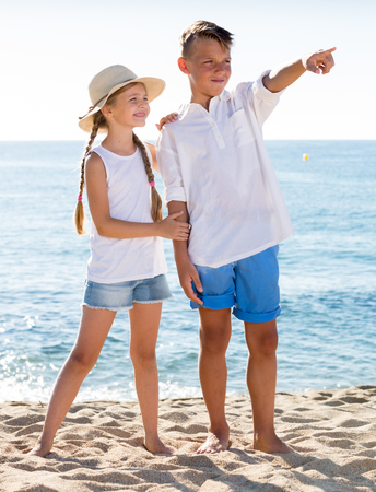 looking aside: two smiling children in elementary school age looking aside and pointing with finger on beach