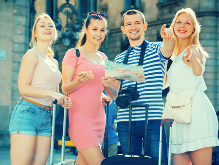 smilling: Group of smilling tourists standing outdoors  with map and  suitcases Stock Photo
