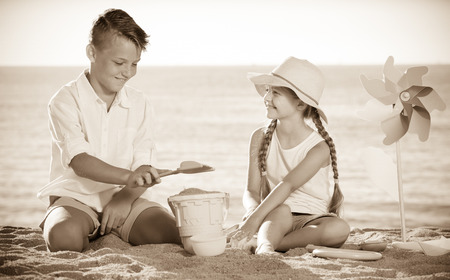 dug: cheerful boy and girl playing with plastic bucket and spade on beach