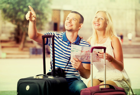 Young traveling couple searching for direction using paper map in town Stock Photo