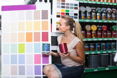 housewares: Smiling young woman looking at color palette in housewares hypermarket