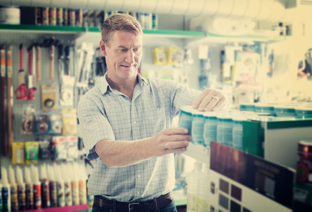 housewares: concentrated man customer choosing paint bucket in housewares hypermarket Stock Photo