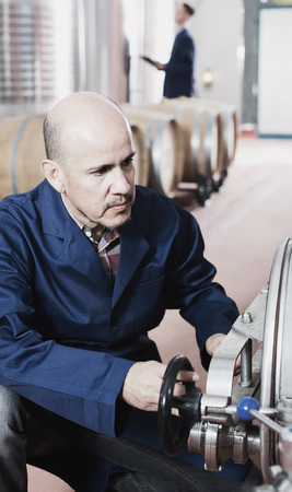 wine register: portrait of mature man working in secondary fermenting section  on winery