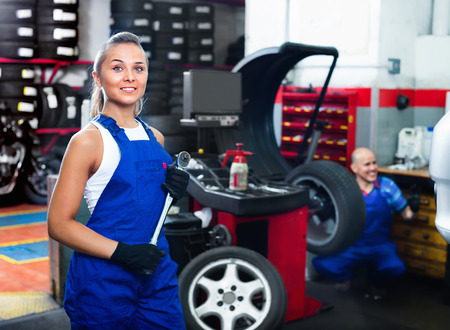 tire fitting: Young cheerful smiling  mechanic woman working on new tire fitting in service point Stock Photo