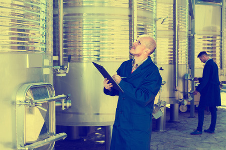 wine register: attentive mature man holding cardboard and checking data at winery fermentation section