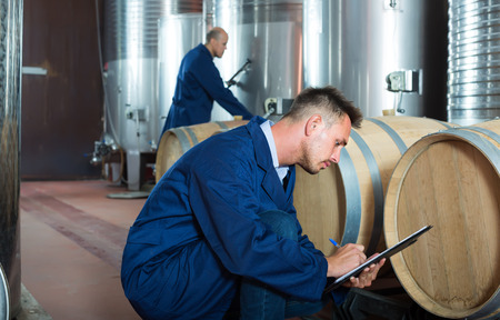 young man working in secondary fermenting section on winery and taking notes