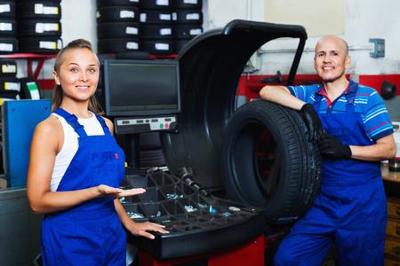 equilibrium: Two positive smiling mechanics operating wheel equilibrium control machinery at auto workshop