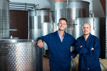 manufactory: Two positive winery employees wearing coats standing in fermentation section on winery manufactory