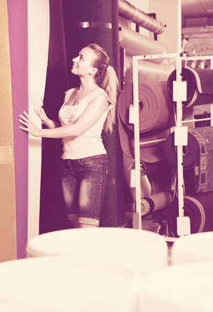 housewares: young woman customer choosing bolt of fitted carpet in housewares hypermarket Stock Photo