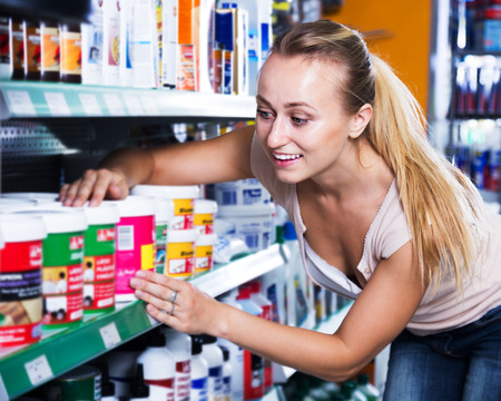 housewares: portrait of positive female customer taking paint can in  housewares department Stock Photo