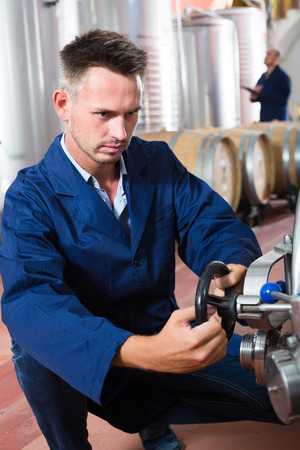 wine register: young man machinery operator working in secondary fermenting section on winery
