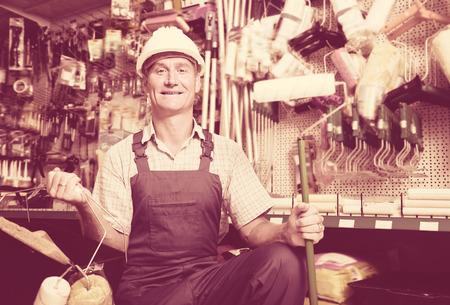 housewares: Portrait of workman in uniform choosing soft roller for painting in housewares hypermarket