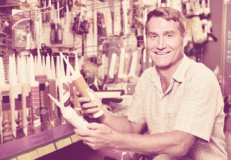 housewares: Portrait of  cheerful smiling male customer selecting sealant bottle in housewares department
