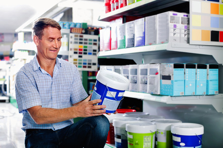 housewares: Portrait of cheerful  positive smiling male customer selecting paint can in housewares department