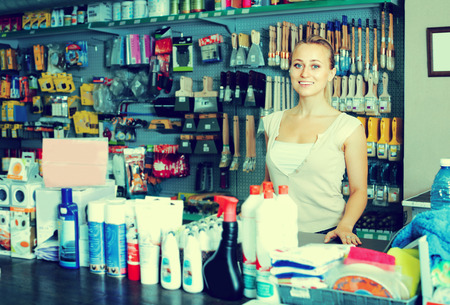 housewares: joyful smiling young woman seller standing at the counter in housewares store Stock Photo