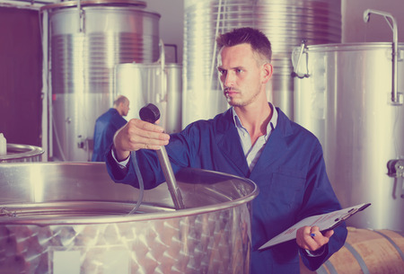 young concentrated man working in secondary fermenting section on winery and taking notes