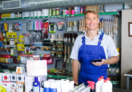 housewares: joyful smiling man seller wearing uniform standing at pay desk in housewares store