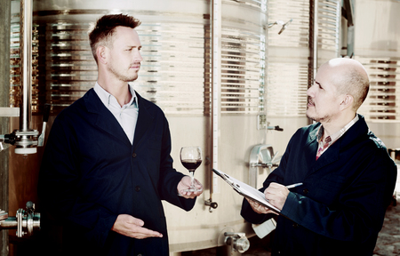 fermentation: two adult winery workers taking notes while discussing wine sample in fermentation section Stock Photo