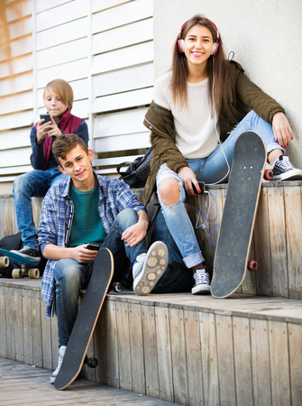 16s: Three teenagers 16s with smartphones in autumn day outdoors Stock Photo