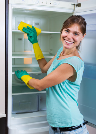 handglove: Positive housewife washing fridge with a detergent at a home kitchen Stock Photo