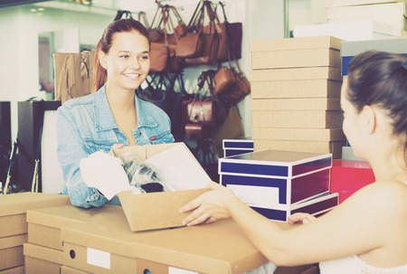 chosen: Cheerful teenager girl taking box with chosen pairs from seller in shoes boutique