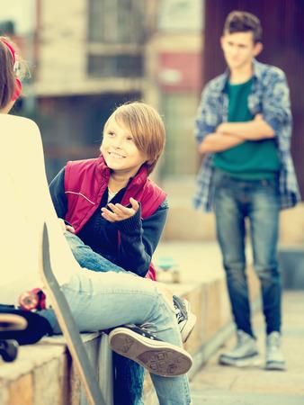 celos: adolescente masculino malestar de pie a un lado de la novia hablando con el muchacho