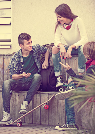blabbing: Portrait of teenage males and american girl talking in autumn day