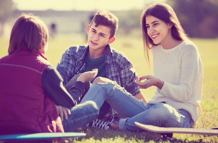 blabbing: Three teenagers hanging out outdoors and discussing something Stock Photo