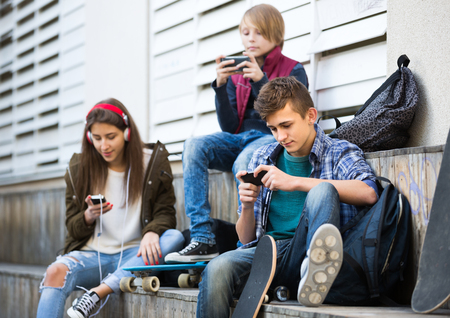 16s: Two teenage males and their girlfriend relaxing with mobile phones outdoor. Focus on guy Stock Photo