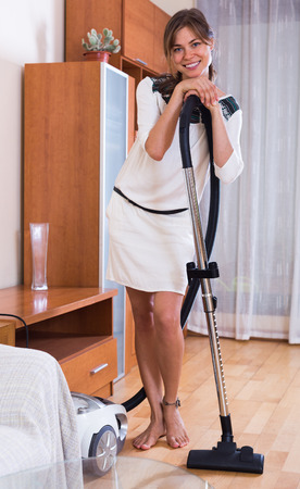cleanup: Smiling young maid doing regular clean-up and using hoover indoors